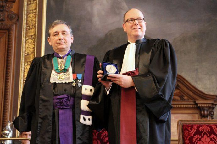 Gilles Pécout (à gauche) et S.A.S. Albert II de Monaco montrant la Grande Médaille de la Chancellerie à l'assemblée lors du DHC du souverain.