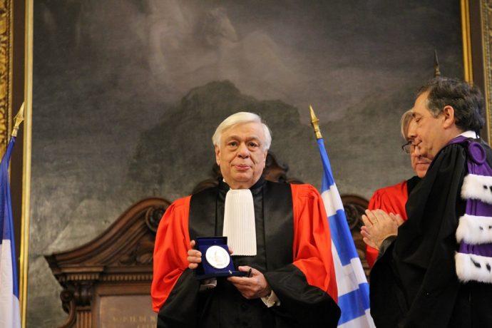 Le Président Prokopis Pavlopoulos montrant la Grande Médaille de la Chancellerie des universités de Paris à l'assemblée.