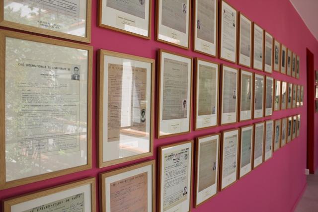 Au mur, des cadres avec les formulaires d'inscription d'anciens résidents.