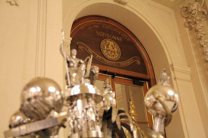 La devise de la Sorbonne : « hic et ubique terrarum » avec au premier plan les masses représentant chacune une discipline.