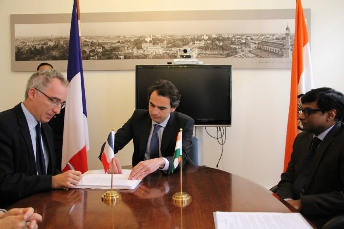 De gauche à droite, François Weil, signant l'acte, maître Guillaume Le Guelinel, notaire, et Son Excellence le Docteur Mohan Kumar.