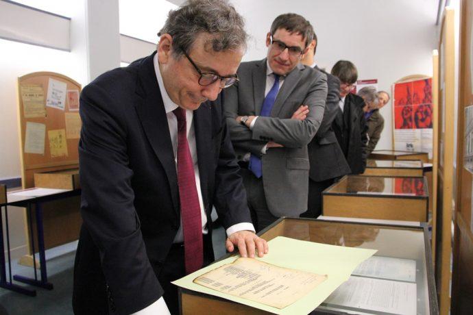 Gilles Pécout, recteur de la région académique Île-de-France, recteur de l'académie de Paris, chancelier des universités, venu inaugurer l'exposition, examine un document d'époque.