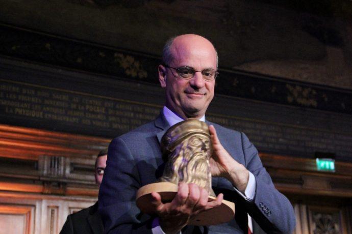 Le ministre Jean-Michel Blanquer montre au public du grand amphithéâtre en Sorbonne le buste en bronze de Léonard De Vinci que les lauréats de la spécialité fonderie du Concours général 2019 lui ont remis sur scène.