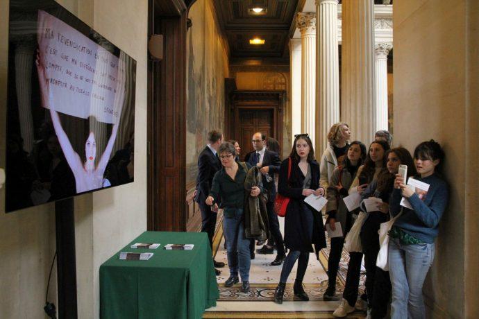 """Le public observant l'une des installations vidéos réalisées par les élèves. Dévoilement des sept portraits de femmes illustres faits par l'artiste C215 pour la Sorbonne : """"Aux grandes femmes, la Sorbonne reconnaissante""""."""